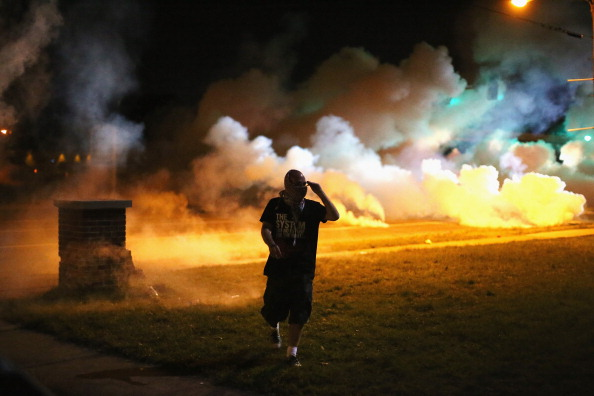 FERGUSON, MO - AUGUST 13:  Demonstrators, protesting the shooting death of teenager Michael Brown, flee as police shoot tear gas into the crowd of several hundred after someone reportedly threw a bottle at the line of police on August 13, 2014 in Ferguson, Missouri. Brown was shot and killed by a Ferguson police officer on Saturday. Ferguson, a St. Louis suburb, is experiencing its fourth day of violent protests since the killing.  (Photo by Scott Olson/Getty Images)